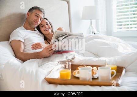 Lächelnde paar lesen Zeitung genießen das Frühstück im Bett - Stockfoto
