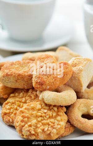 Nahaufnahme einer Auswahl an verschiedenen Butterkekse in eine weiße Platte, auf einem gedeckten Tisch mit einigen - Stockfoto