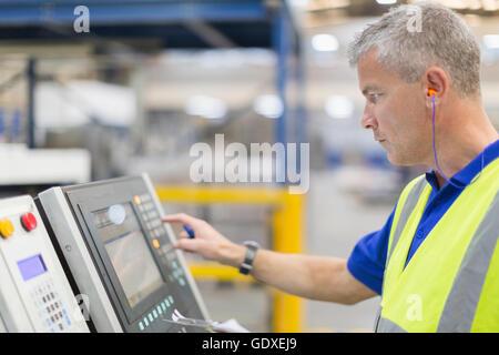 Arbeiter, die Bedienung von Maschinen am Bedienfeld im Stahlwerk - Stockfoto