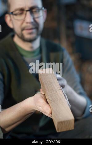 Männliche Bogenmacher Qualitätsprüfung des Holzes in Werkstatt, Bayern, Deutschland - Stockfoto