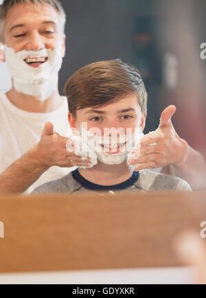 Vater helfen Sohn vorgibt, im Badezimmerspiegel rasieren - Stockfoto