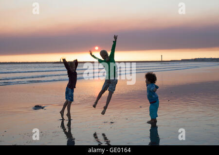 Drei Kinder springen am Strand bei Sonnenuntergang, Viana do Castelo, Norte Region, Portugal - Stockfoto