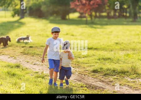 Zwei Jungs gehen Arm in Arm auf Wanderweg - Stockfoto