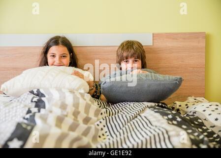 Jungen und Mädchen sitzen im Bett versteckt unter abdeckt - Stockfoto