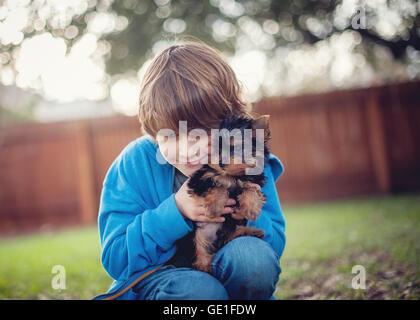 Junge seine Yorkie Welpen Hund kuscheln - Stockfoto