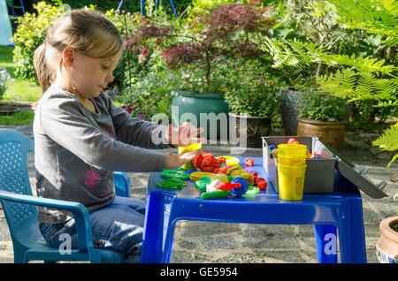 Drei Jahre alten Mädchen spielen mit Play-Doh Modellierung Kitt. VEREINIGTES KÖNIGREICH. Draußen im Garten. - Stockfoto