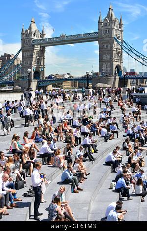 """Heißer Tag für Büroangestellte & Touristen im Sommer mittags Pause rund um """"The Scoop"""" Amphitheater London Tower - Stockfoto"""