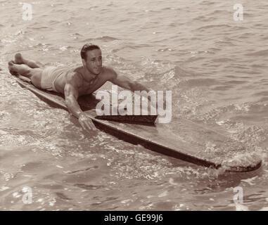 """Weltmeister Surfer/Paddler Gene Smith (aka """"Tarzan"""") auf hölzernen Surfbrett während fast 100 Mile Paddel von Honolulu - Stockfoto"""