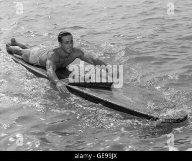 """Champion Surfer/Paddler Gene """"Tarzan"""" Smith auf hölzernen Surfbrett während fast 100 Mile Paddel von Honolulu nach - Stockfoto"""