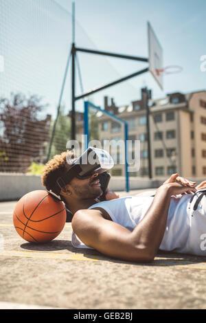 Junges Paar mit virtual-Reality-Brille, Köpfe auf Basketball ruht - Stockfoto