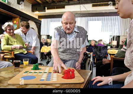 Bewohner und Krankenschwestern spielen Brettspiele in einem Pflegeheim - Stockfoto