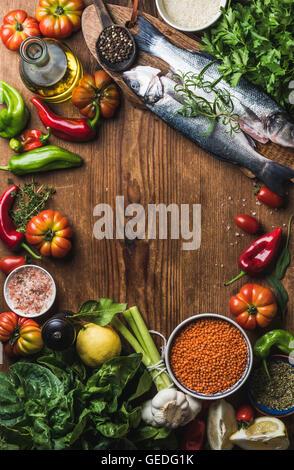 Rohe ungekochte Wolfsbarsch Fisch, Gemüse, Getreide, Kräutern, Gewürzen und Olivenöl auf rustikalen hölzernen Schneidebrett - Stockfoto