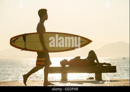 RIO DE JANEIRO - 5. April 2016: Eine junger Carioca brasilianische Surfer trägt seinem Surfbrett auf der Copacabana - Stockfoto