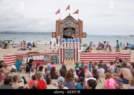 Traditionelle Punch and Judy zeigen am Strand von Weymouth Dorset UK mit kleinen Kindern und ihren Eltern beobachten. - Stockfoto