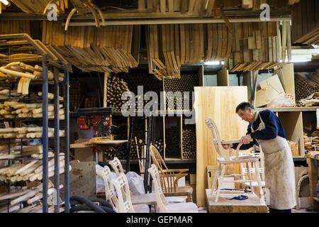 Mann stehend in einer Tischlerei, arbeiten auf einem Holzstuhl. - Stockfoto