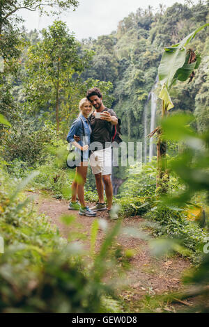 Junges Liebespaar unter Selbstporträt mit ihrem Handy. Mann und Frau im Wald nehmen Selfie. - Stockfoto