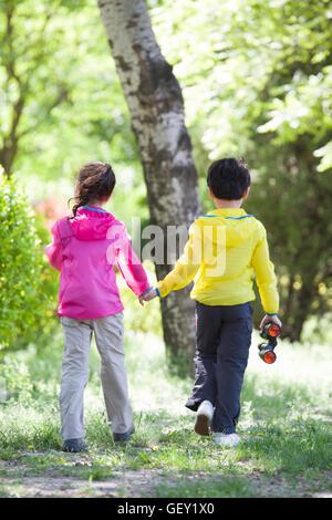 Chinesische Kinder Hand in Hand wandern in Wäldern - Stockfoto