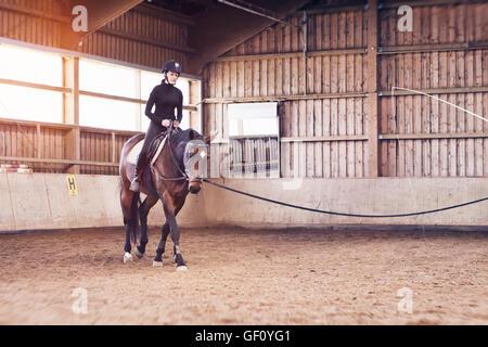 Junge Frau, die ihr Pferd in eine Reithalle am Longieren Zügel gehalten durch einen Dritten mit Textfreiraum - Stockfoto
