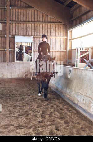 Junge Frau Reiter zu Fuß ihr Pferd im Haus am Rand der Schule Reithalle nähert sich die Kamera während der Festi - Stockfoto