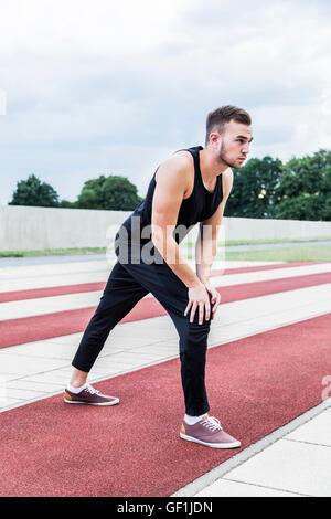 Junge Sportler in schwarz Sportbekleidung Vorbereitung für Training oder Wettkämpfe auf einem roten Laufstrecke - Stockfoto