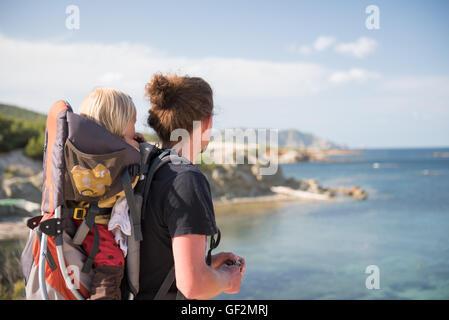 Vater und Baby Tochter in Rucksack-Träger Blick auf malerische Aussicht. Familienreisen - Stockfoto