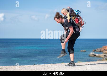 Vater und Baby Tochter Wandern mit Rucksack-Träger in schöner Landschaft - Stockfoto