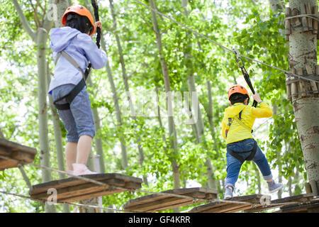 Glückliche chinesische Kinder spielen im Tree Top Adventure park - Stockfoto