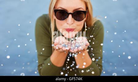 Porträt von attraktiven jungen Frau bläst glitzert hautnah. Caucasian Female Model Spaß auf blauem Hintergrund. - Stockfoto