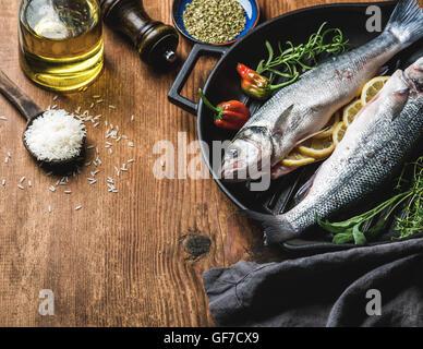 Zutaten für Cookig gesunden Fisch zum Abendessen. Rohe ungekochte Seebarsch mit Reis, Olivenöl, Zitrone, Kräutern - Stockfoto