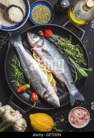 Zutaten für Cookig gesunden Fisch zum Abendessen. Rohe ungekochte Seebarsch mit Reis, Zitrone, Olivenöl, Kräuter - Stockfoto