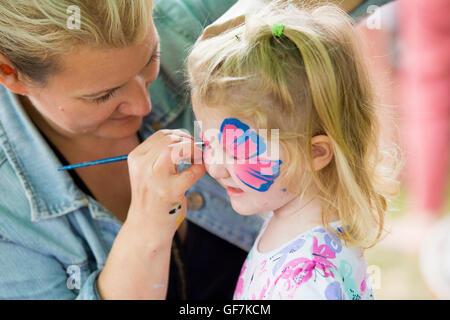 Professionelles Schminken Schmink / Make-up-Künstler malt ein sechs Jahr alt / 6 Jahre altes Kind Gesicht auf einer - Stockfoto