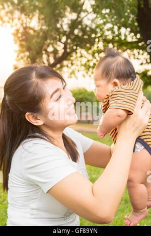 asiatische 2 Monate baby Gefühl glücklich und Lächeln mit ihrer Mutter in den Garten und den Sonnenuntergang Hintergrund