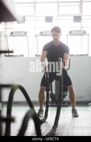 Junger Mann mit kämpfen Seil im Fitness-Studio trainieren - Stockfoto