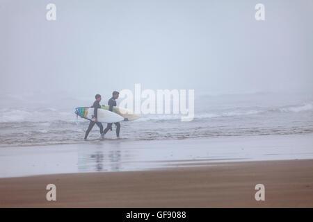 Kornische Surfer Rückkehr aus der Brandung im Whitsand Bay befindet sich in Cornwall, England, rollt UK als Nebel. - Stockfoto