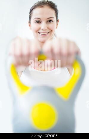 EIGENTUM FREIGEGEBEN. -MODELL VERÖFFENTLICHT. Lächelnde junge Frau mit Kettlebell im Fitness-Studio, Porträt. - Stockfoto