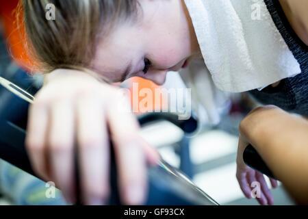 EIGENTUM FREIGEGEBEN. -MODELL VERÖFFENTLICHT. Nahaufnahme der jungen Frau, die ihren Kopf auf Heimtrainer im Fitnessstudio - Stockfoto