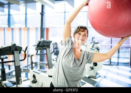 EIGENTUM FREIGEGEBEN. -MODELL VERÖFFENTLICHT. Ältere Frau mit Ball im Fitness-Studio trainieren. - Stockfoto