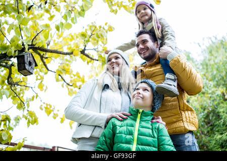 -MODELL VERÖFFENTLICHT. Familie zusammen im Park lächelnd und wegsehen, Vogelhaus im Hintergrund. - Stockfoto