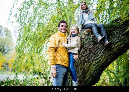 -MODELL VERÖFFENTLICHT. Vater mit Tochter, Mutter saß am Baum, Lächeln, Porträt. - Stockfoto
