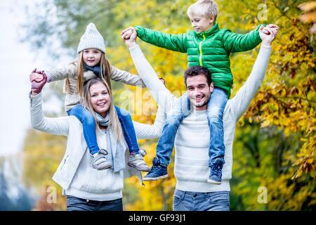 -MODELL VERÖFFENTLICHT. Eltern mit ihren Kindern auf Schultern, im Herbst, lächelnd. - Stockfoto