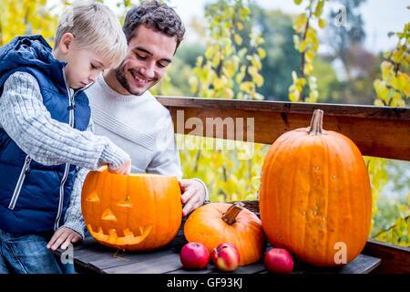 -MODELL VERÖFFENTLICHT. Vater und Sohn machen Halloween-Kürbis. - Stockfoto