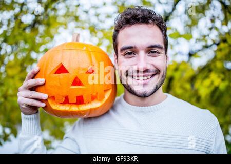 -MODELL VERÖFFENTLICHT. Porträt des jungen Mann, der Halloween-Kürbis hält. - Stockfoto