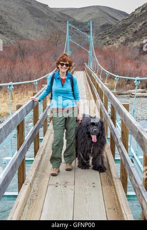 Frau und Neufundland Hund auf Hängebrücke über den Yakima River bei Umtanum - Stockfoto