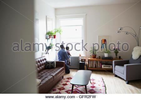Vater und Sohn suchen Wohnzimmerfenster - Stockfoto