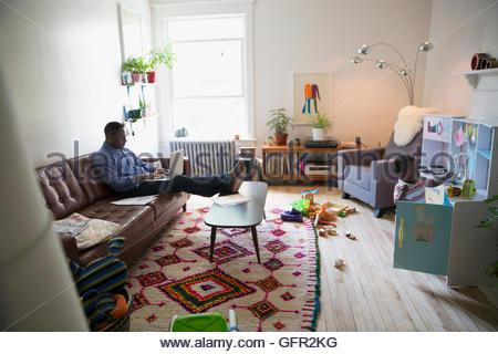 Vater mit Laptop in der Nähe von Sohn spielt im Wohnzimmer - Stockfoto
