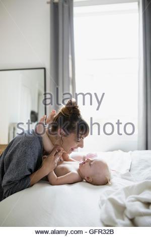 Spielerische Mutter und Tochter von Angesicht zu Angesicht auf Bett - Stockfoto