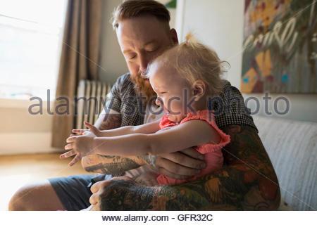 Vater mit Tätowierungen, die weinende Tochter hielt - Stockfoto