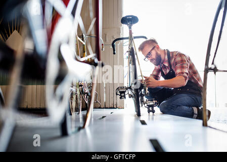 Ein Mann, der arbeitet in einer Fahrradwerkstatt - Stockfoto