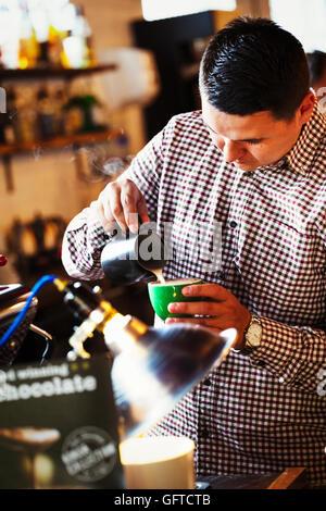 Ein Mann, ich mache eine Tasse Kaffee mit Milch - Stockfoto
