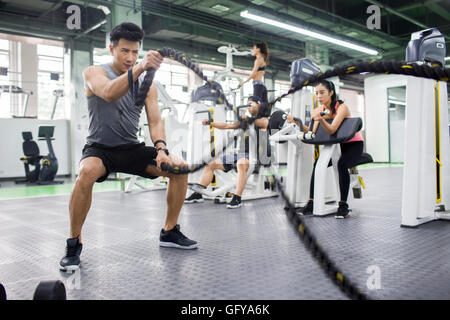 Junge chinesische Mann Training mit Seil im Fitnessstudio zu kämpfen - Stockfoto